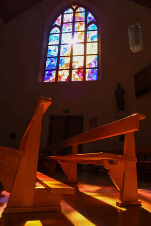 pews: Modern stained glass windows reflecting colors on church pews of Castle church at Interlaken on Switzerland