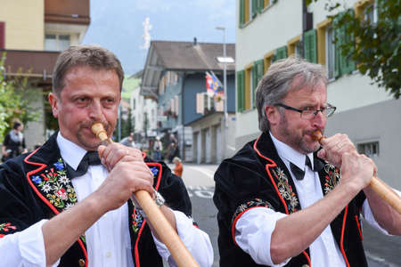 alphorn: Kerns, Switzerland - 1 October 2016: People wearing traditional clothes and playing the alphorn at Kerns on the Swiss alps