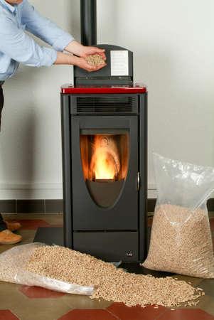 Moderna estufa de pellets doméstica con una llama y bolsas llenas de gránulos de partículas en llamas Foto de archivo