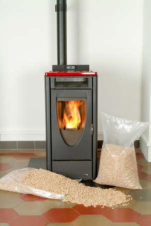 Moderne binnenlandse pelletkachel met een brandende vlam en zakken vol deeltje pellets