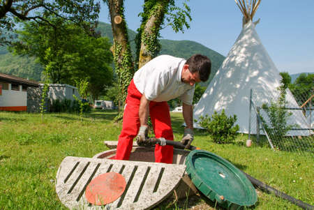 gas supply: Melano, Switzerland -20 May 2005: worker making gas supply on a tank in the garden of a house at Melano on Switzerland