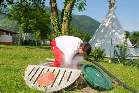 Melano, Switzerland -20 May 2005: worker making gas supply on a tank in the garden of a house at Melano on Switzerland