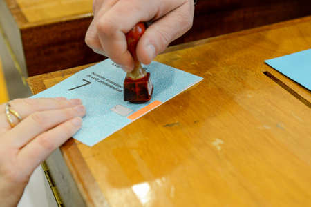 parliamentary: Lugano, Switzerland - 11 april 2016: Hand  validating a voting ballot at the municipal election of Lugano on Switzerland