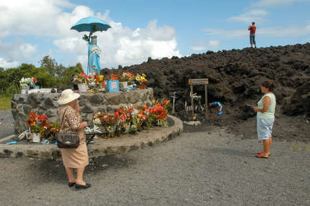 La Reunion island, France - 29 December 2002: people visiting the statue of Godmother with umbrella at the sanctuary of the lava eruption on La Reunion island, France Editorial