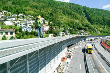 ビッソーネ, スイス - 2010 年 5 月 20 日: ビスソーンのスイス連邦共和国の高速道路の遮音壁のインストール中に労働者 報道画像