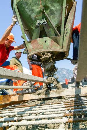 crane bucket: Bissone, Switzerland - 26 April 2011: Street workers pouring cement into a highway construction at Bissone on Switzerland