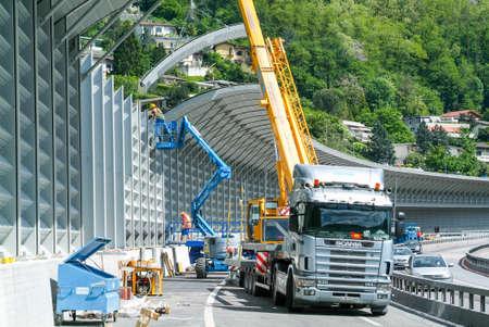 Bissone, Zwitserland - 20 mei 2010: Werknemers tijdens de installatie van geluidsschermen op de snelweg bij Bissone op Zwitserland