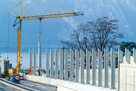 ビッソーネ, スイス - 2010 年 3 月 12 日: ビスソーンのスイス連邦共和国の高速道路の遮音壁のインストール中に労働者