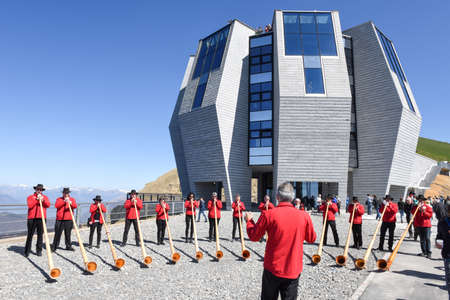 alphorn: Mount Generoso, Switzerland - 8 April 2017: People playing the alphorn in front of the modern restaurant at Mount Generoso on the Swiss alps