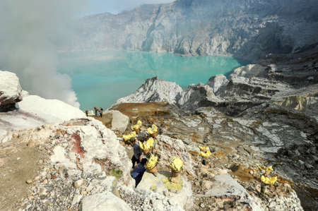 sulphur: Vulcano Ijen, Indonesia - 5 February 2013: Miners with their sulfur crops climb the ijen crater on the island of Java, Indonesia Editorial