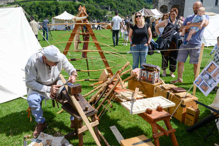 antiques: Bellinzona, Switzerland - 21 May 2017: Man who builds a bow at the medieval market on Castelgrande castle at Bellinzona on the Swiss alps