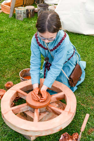 Bellinzona, Switzerland - 21 May 2017: girl making pottery on a medieval happening at Castelgrande castle at Bellinzona on the Swiss alps Editorial
