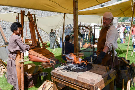 medieval blacksmith: Bellinzona, Switzerland - 21 May 2017: Blacksmith who is forging a sword at the medieval market on Castelgrande castle at Bellinzona on the Swiss alps