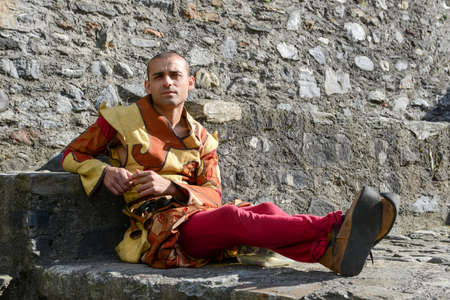 historical events: Bellinzona, Switzerland - 21 May 2017: man on medieval clothes sitting on the walls of Castelgrande castle at Bellinzona on the Swiss alps Editorial