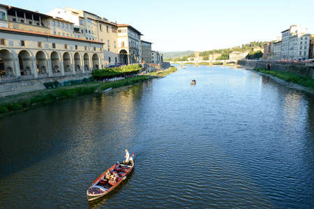 Firenze, Italy - 5 July 2017: people sailing with a boat on river Arno at Florence on Italy.