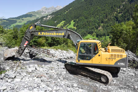 Engelberg, Switzerland - 30 July 2017: digger who rearranges a bed of a river after a landslide at Engelberg on the Swiss alps Editorial