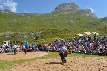 Engstlenalp, Switzerland - 4 August 2018: Two Swiss taking part in a traditional wrestling match (called Schwingen) at Engstlenalp on the Swiss alps Editorial