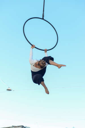 Lugano, Switzerland - 15 July 2016 - Lugano, Switzerland - 15 July 2016 -  Woman acrobat on a hula hoop does tricks at Buskers Festival in Lugano, Switzerland