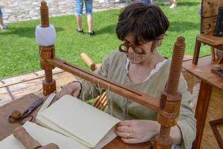 Bellinzona, Switzerland - 27 May 2018: bookbinder at the medieval market on Castelgrande castle at Bellinzona on the Swiss alps Editorial