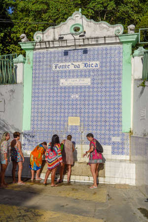 Itaparica island, Brazil - 4 February 2019: people drinking water of colonial fountain at Itaparica island on Brazil Editoriali