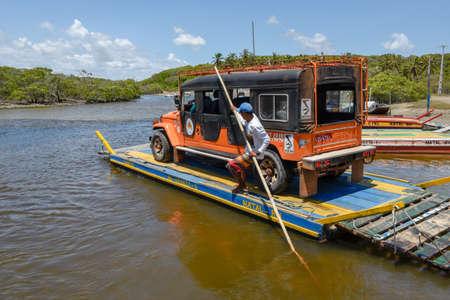 Pipa, Brazil- 23 January 2019: man trasporting a car on a raft in the river near Pipa on Brazil