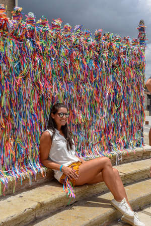 Salvador, Brazil - 5 February 2019: woman posing in front of wish ribbons at Bonfim church in Salvador Bahia on Brazil Editorial
