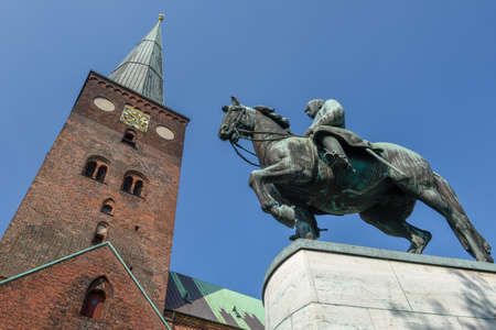 Statue and 13th century Cathedral at Aarhus on Denmark 免版税图像