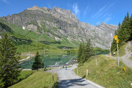 people hiking at lake Truebsee over Engelberg on the Swiss alps Stock Photo