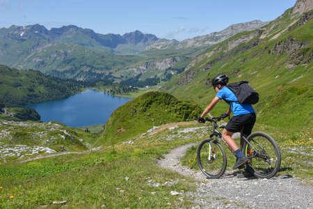Jochpass, Suiza - 4 de agosto de 2018: el hombre en su bicicleta de montaña bajando por el camino de Jochpass sobre Engelberg en los Alpes suizos Editorial