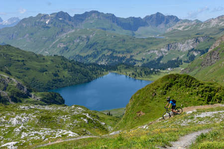 Jochpass, Switzerland - 4 august 2018: man on his mountain bike going down the path from Jochpass over Engelberg in the Swiss Alps Editorial