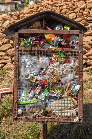 Overflowing full garbage bin