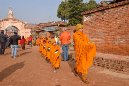 Bhaktapur, Nepal - 28 January 2020: young Buddhist monks walking in morning alms at Bhaktapur on Nepal