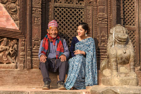 Bhaktapur, Nepal - 28 January 2020: beautiful woman with old man on traditional clothes at Bhaktapur in Nepal