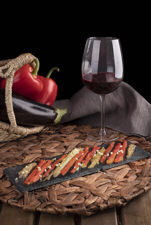 Escalivada with organic food vegetables in wicker basket on rustic wooden table with wine glass. Vertical view.