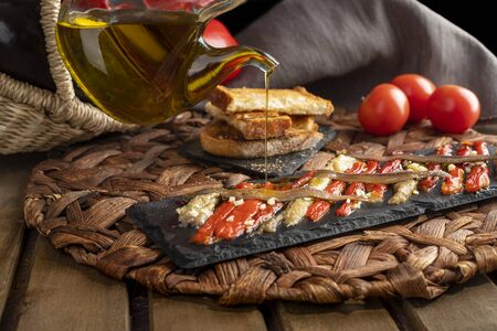 Escalivada washed down with virgin olive oil and vegetables in wicker basket on the rustic wooden table