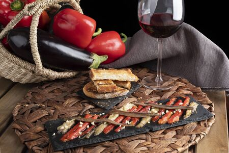 Escalivada with organic food vegetables in wicker basket on rustic wooden table with wine glass. Horizontal view.