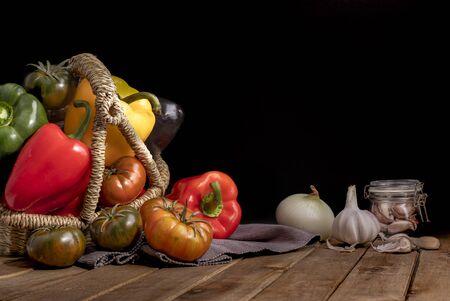 Organic food vegetables in wicker basket on rustic wooden table thing on black background. Reklamní fotografie
