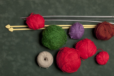multicolored yarn and knitting needles for knitting on a green background