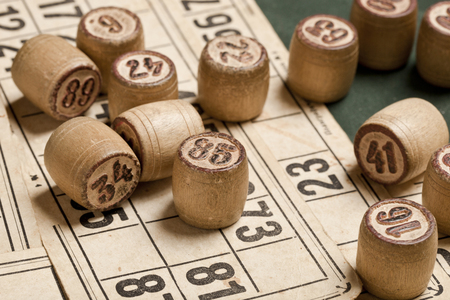 Table game Bingo. Wooden Lotto barrels with bag, playing cards for Lotto games, games for family on green background Imagens