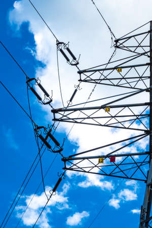 Electric pylons of high voltage lines against a blue sky with white clouds. Photo taken in daylight. Stock fotó