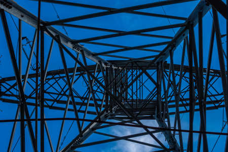 Electric pylons of high voltage lines against a blue sky with white clouds. Photo taken in daylight.