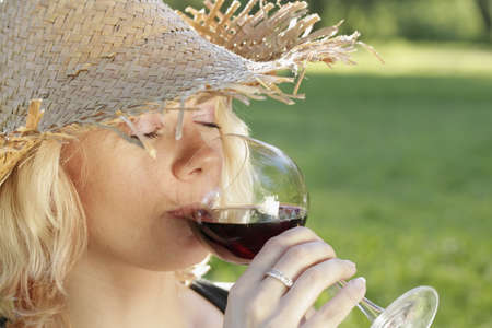 young woman with sun hat drinking red wine