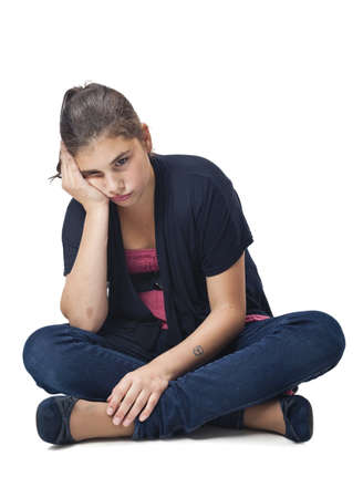 sad and pensive girl sitting cross-legged Stock Photo