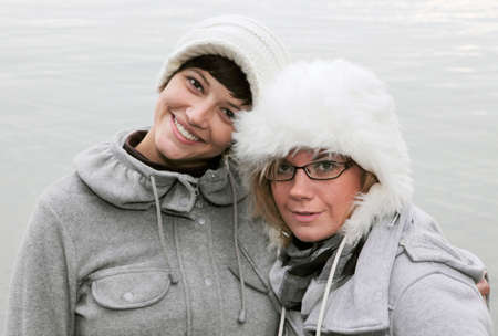 young pretty women with white caps in winter outfit Stock Photo - 8572683