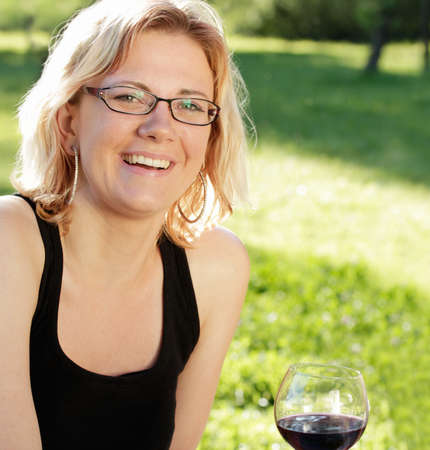 Young woman laughing and red wine drinking photo