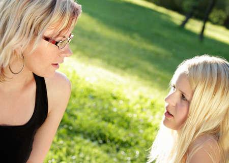 pubertad: Dos mujeres j�venes, hablando en serio, el verano disparo al aire libre