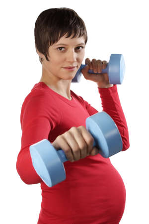Young pregnant woman with weights. Studio shot against a white background.