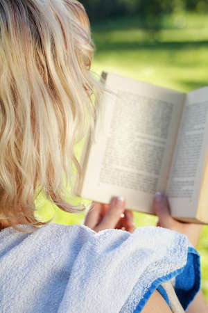 Young blonde woman in the park reading a book - rear view photo