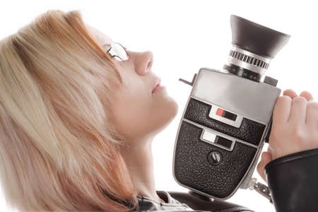 blonde, young woman holding a movie camera, side view photo