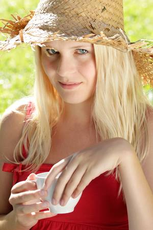 blond teenage girl with cup and straw hat looking up Stock Photo - 8667418